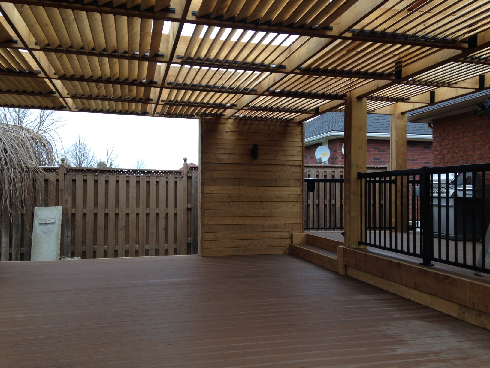 Wood accent walls and louvered wood pergola